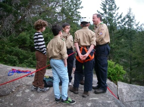 After explaining how to set up our anchor, the boys are taught how to clip a belay/rappel device (ATC Guide) into the rope for rappelling.
