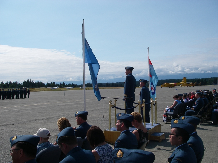 LCol Robinson looks over his Squadron with pride one last time before transferring command to LCol Kenny. 442 Search & Rescue Squadron planes and helicopters sit in readiness at the other end of the runway: