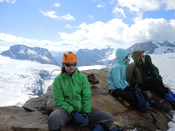 The four gals on the summit team (left to right: Meredith, Jessica, Svetlana and Emerald) relaxing with (left to right) Mt. Macoun (3030 m), Mt. Topham (2900 m) and Mt. Fox (3196 m) rising in the distance behind them.