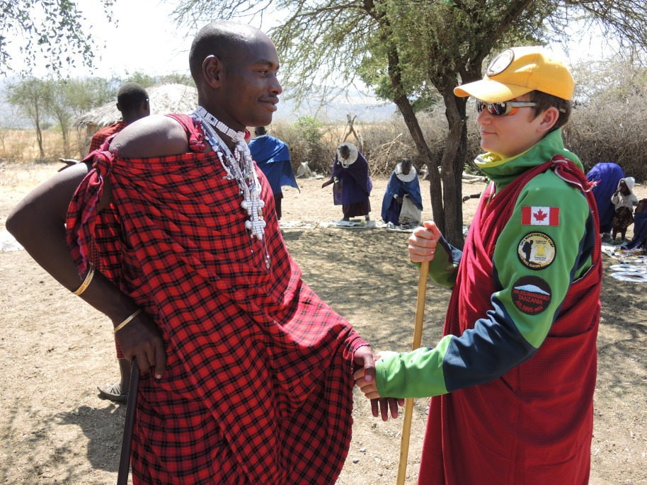 Scout Simon (after being made an honourary Maasai Warrior in recognition of his climb of Kilimanjaro) shakes hands with the Scout left handshake.  The Maasai recognize the left handshake and name of the founder of Scouting in the birthplace of Scouting: Africa.